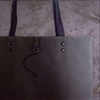 retail packaging design, black medium shopping bag, close up opening fastening flat table top | British Fashion Retail Brand – Magnum London :: packaging