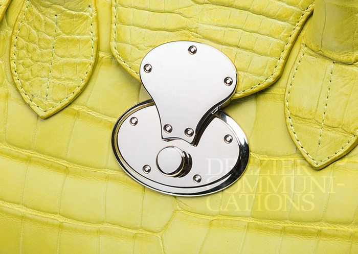 women's lemon yellow hand bag close up chrome opening buckle table top, accessories photography on cement background styling art direction retouched colour management | Garment Merchandising Company in Hong Kong : : Styling and Imaging of Apparel Made in and Imported from Italy Reselling through e-Commerce